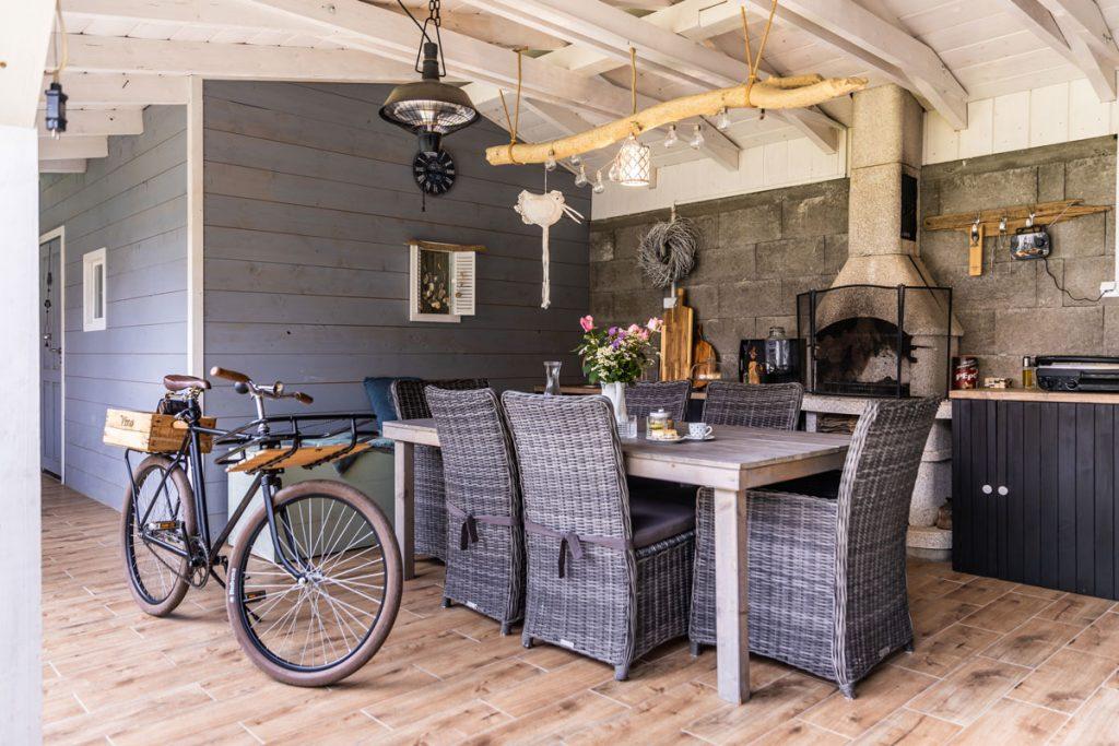 Letná kuchyňa so záhradným krbom pod dreveným prístreškom