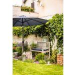 Kútik v záhrade s drevenou lavičkou, slnečníkom, záhonmi a tehlovým múrikom.