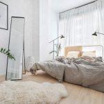 Spálňa v škandinávskom štýle s kovovou posteľou, čiernymi lampami a kožušinou.