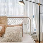 Detail kovovej postele s dekoráciou v podobe lapača snov a s čiernou kovovou lampou.