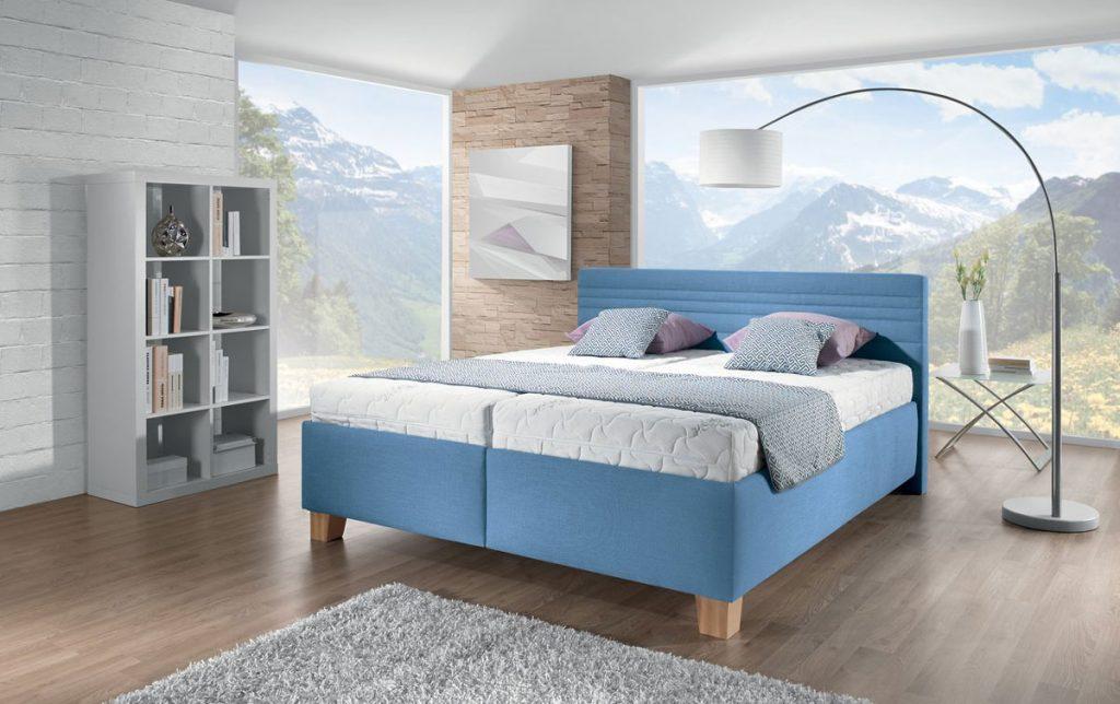 čalúnená posteľ v modrej farbe