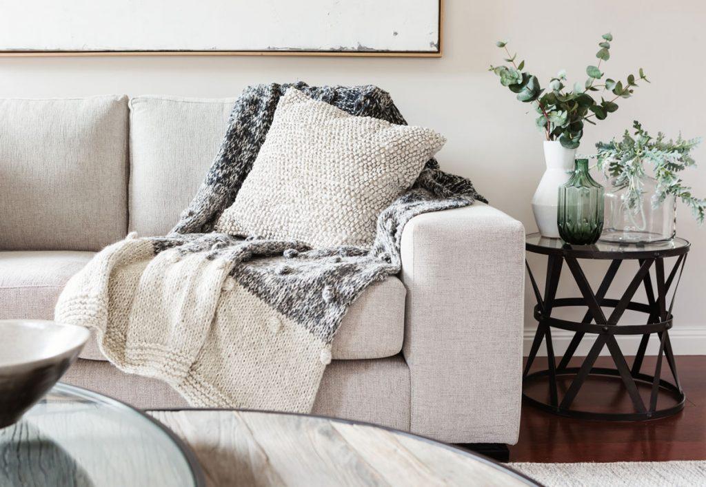 Zorientujte sa v textilných materiáloch: Detail sedačky v prírodnom štýle s mäkkou dekou a vankúšom