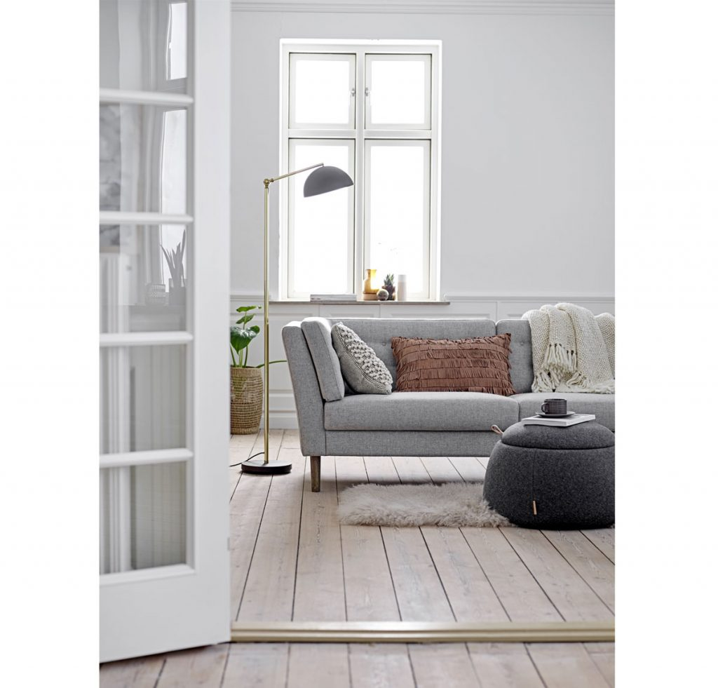 Sivá a drevo v interiéri: biela maľovka, drevená podlaha a sivá sedačka