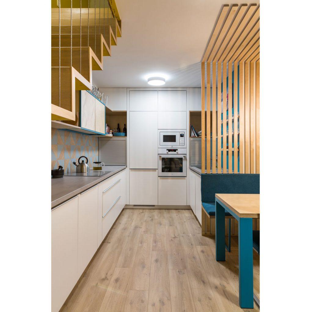 Dizajnérske riešenie bielej kuchyne pod schodmi mezonetového bytu