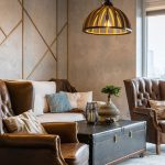 Vintage obývačka so svetlou sedačkou, koženými kreslami a truhlicou slúžiacou ako stolík a dekórom na stene z drevených líšt