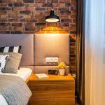 Pohľad na drevený nočný stolík s posteľou a tehlovou stenou.