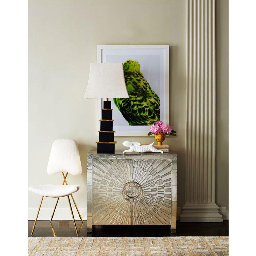 Interiér so striebornou komodou, bielou stoličkou a lampou so zlatými prvkami