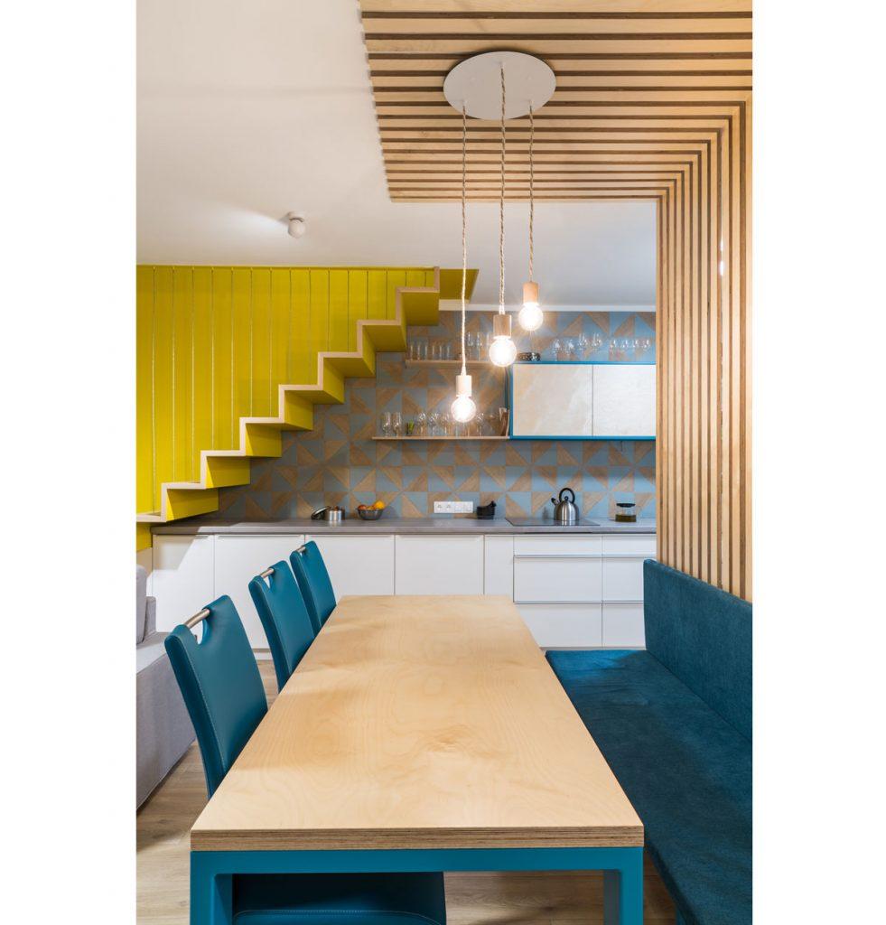 Riešenie spoločenskej zóny pod schodiskom mezonetového bytu s kuchynskou linkou, jedálenským kútom a obývačkou
