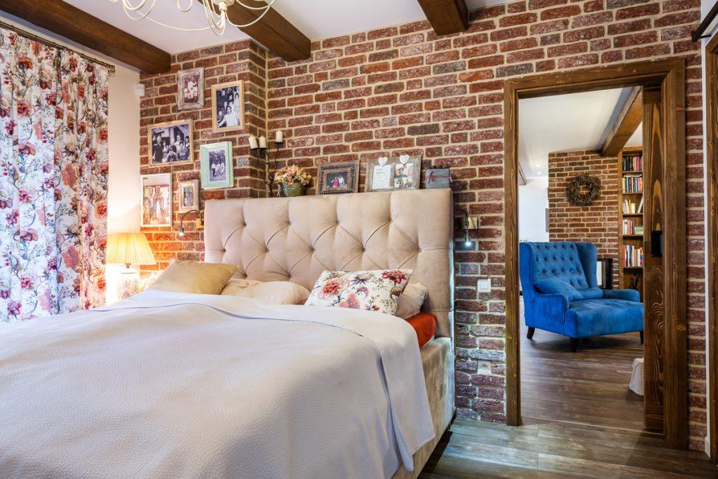 Romantická spálňa vo vidieckom štýle s čalúnenou posteľou, tehlovou stenou, stropnými trámami a kvetinovými vzormi