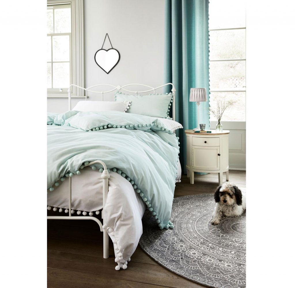 Spálňa s vintage kovovou posteľou, pastelovými farbami a komodou