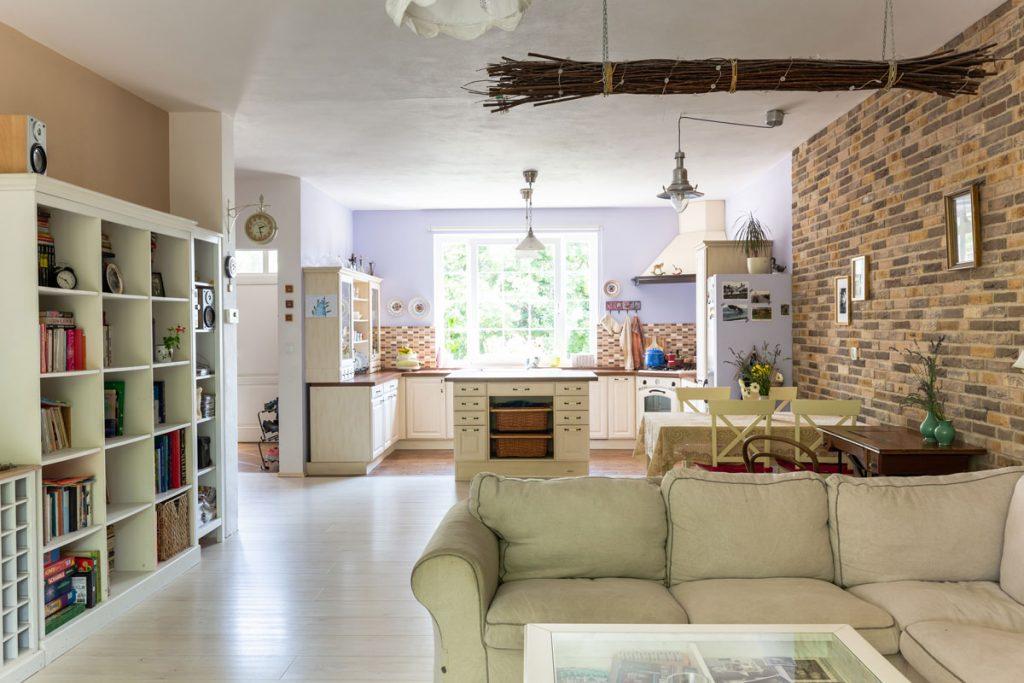 otvorená denná zóna s kuchyňou, jedálňou a obývačkou vo vidieckom štýle v smotanových farbách a s tehlovou stenou