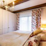 Vidiecka spálňa s kvetinovými vzormi a bielou šatníkovou skriňou