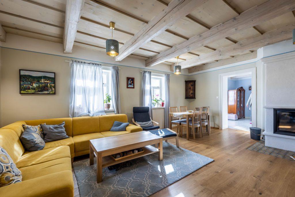 Obývačka v modernom vidieckom štýle so žltou sedačkou, jedálenským kútom, krbom a stropom s drevenými trámami.