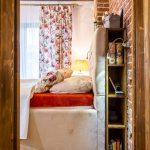 romantická vidiecka spálňa s čalúnenou posteľou, ktorá má za čelom postele umiestnené odkladacie priestory