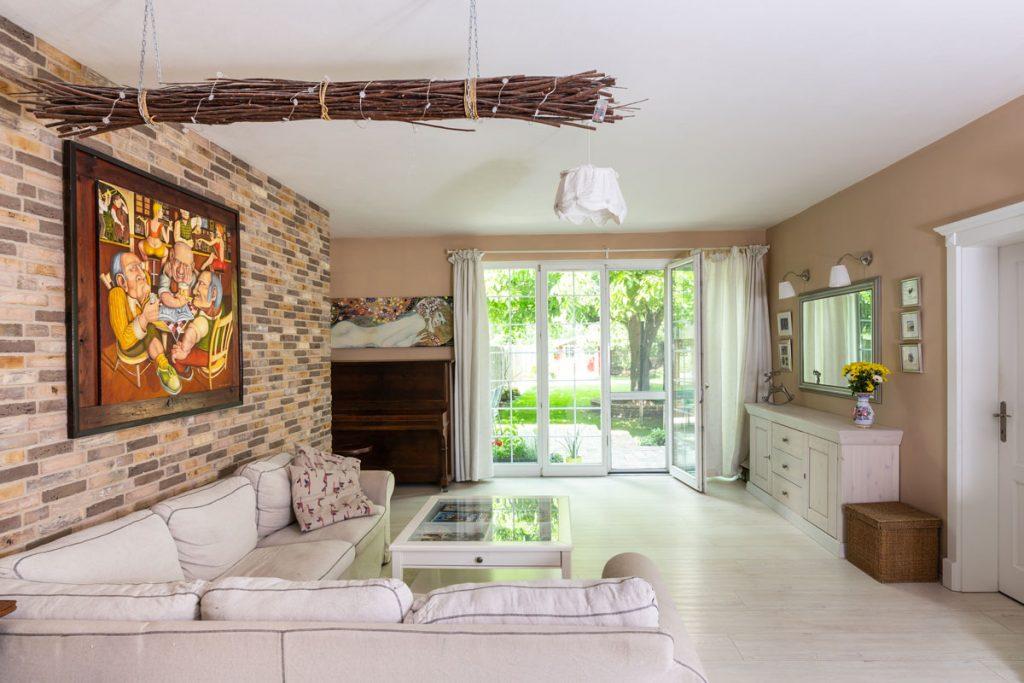 Obývačka v modernom vidieckom štýle v smotanovej farbe, s tehlovou stenou a východom na záhradu