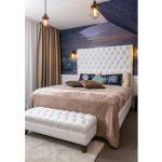 Vintage spálňa so svetlou čalúnenou posteľou a lavicou v kontraste s tmavou tapetou za čelom postele