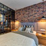 Industriálna spálňa so samostatným šatníkom, tehlovou stenou a posteľou v severskom štýle