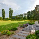 Záhrada s veľkým trávnikom určeným na hru a oddych, v popredí s drevenou terasou a okrasnými záhonmi.