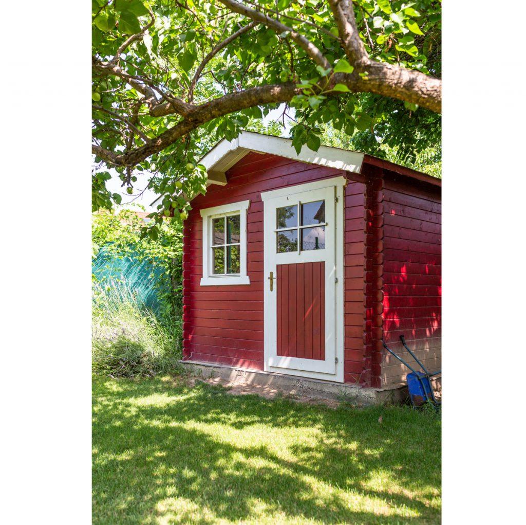 záhradný domček natretý v škandinávskej kombinácii červenej a bielej farby