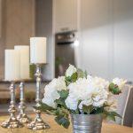 Stôl so striebornými svietnikmi a vedierkom s kvetmi