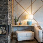 Obývačka s krbom a svetlou pohovkou a so stenou s betónovou stierkou ozvláštnenou drevenými lištami