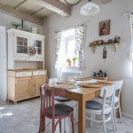 Interiér s jedálenským stolom a príborníkom vo vidieckom štýle a s historizujúcou podlahou