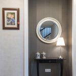 zátišie v chodbe s vintage okrúhlym zrkadlom a vintage stolíkom