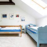 chlapčenská izba v podkroví s modrou posteľou a posteľou s prirodzeným vzhľadom dreva
