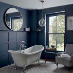 Interiér v modrej farbe, s veľkým okrúhlym zrkadlom, vaňou na nožičkách a ušiakom