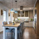 Vintage kuchyňa s nádychom vidieka, s bielou kuchynskou zostavou, ostrovčekom, jedálenským stolom a čalúnenými stoličkami, kovovými lustrami, nástennými svietnikmi a otapetovaným stropom so vzorom vtáčikov