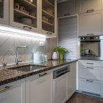 Detail bielej kuchyne vo vidieckom štýle so vstavanými spotrebičmi.