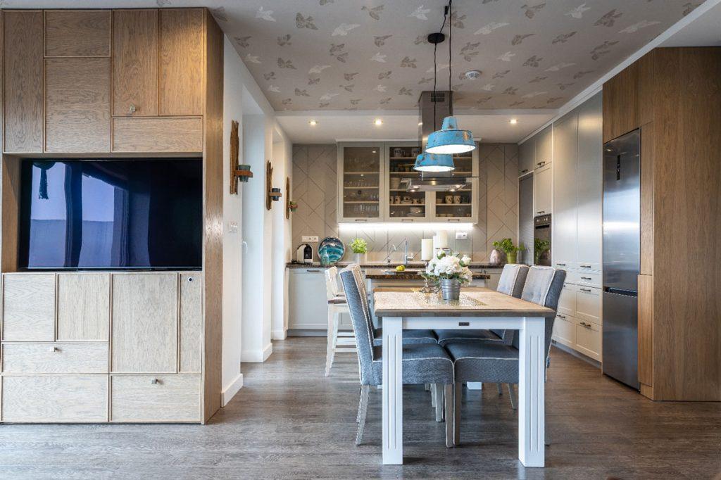 Otvorený priestor kuchyne, ktorý plynule prechádza do obývačky s TV stenou so skrytými úložnými priestormi