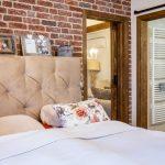 Romantická vidiecka spálňa so stenou z tehlového obkladu a posuvnými dverami do kúpeľne a obývačky