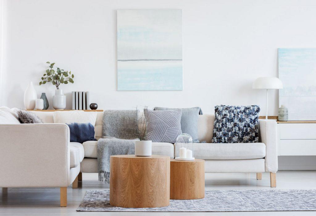 Sivá a drevo v interiéri: Svetlosivá sedačka so sivými vankúšmi a drevené stolíky