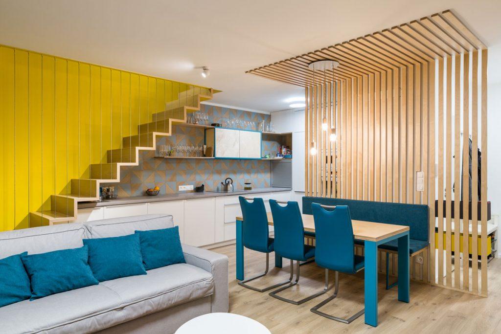 Dizajnérske riešenie otvoreného priestoru obývačky, jedálne a kuchyne v mezonetovom byte s kuchynskou linkou pod schodiskom