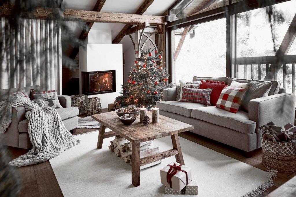 Obývačka vo vidieckom dome so zariadením v odtieňoch sivej a v prírodnom štýle a s drevenými trámami, vyzdobená na Vianoce