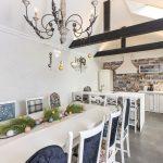 kuchyňa v provensalskom štýle so vzorovanými kachličkami, bielou linkou, ostrovčekom a jedálenským bielym stolom s rôznymi druhmi čalúnených stoličiek