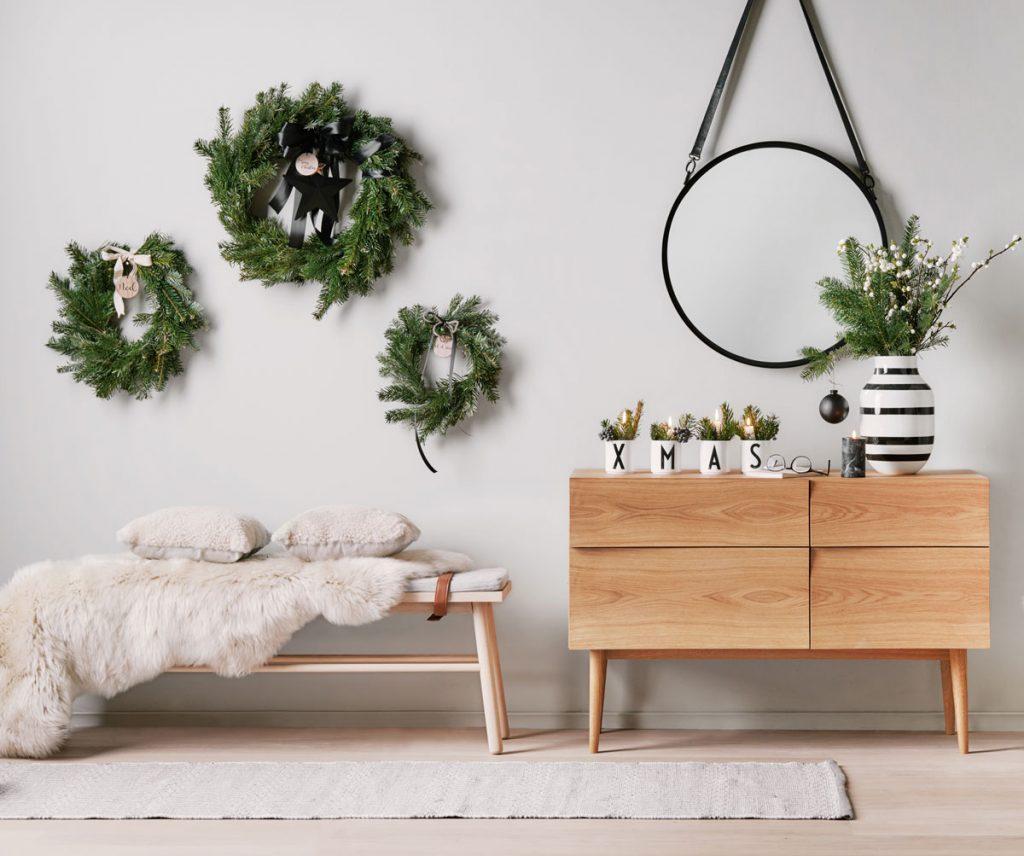 Menej tradičná vianočná výzdoba: Ihličie v podobe vencov zavesených na stene a vo váze
