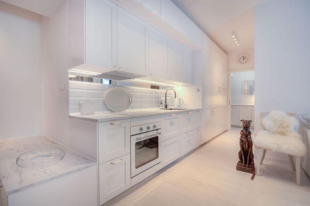 Moderná biela kuchyňa s prechodom do práčovne