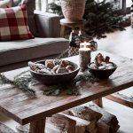 Drevený stolík vo vianočnej obývačke s vianočným pečivom, čečinou a sviečkami