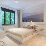 Biela spálňa s pracovným kútikom a s obrazom lesov, ktoré opticky dodávajú menšej miestnosti priestor