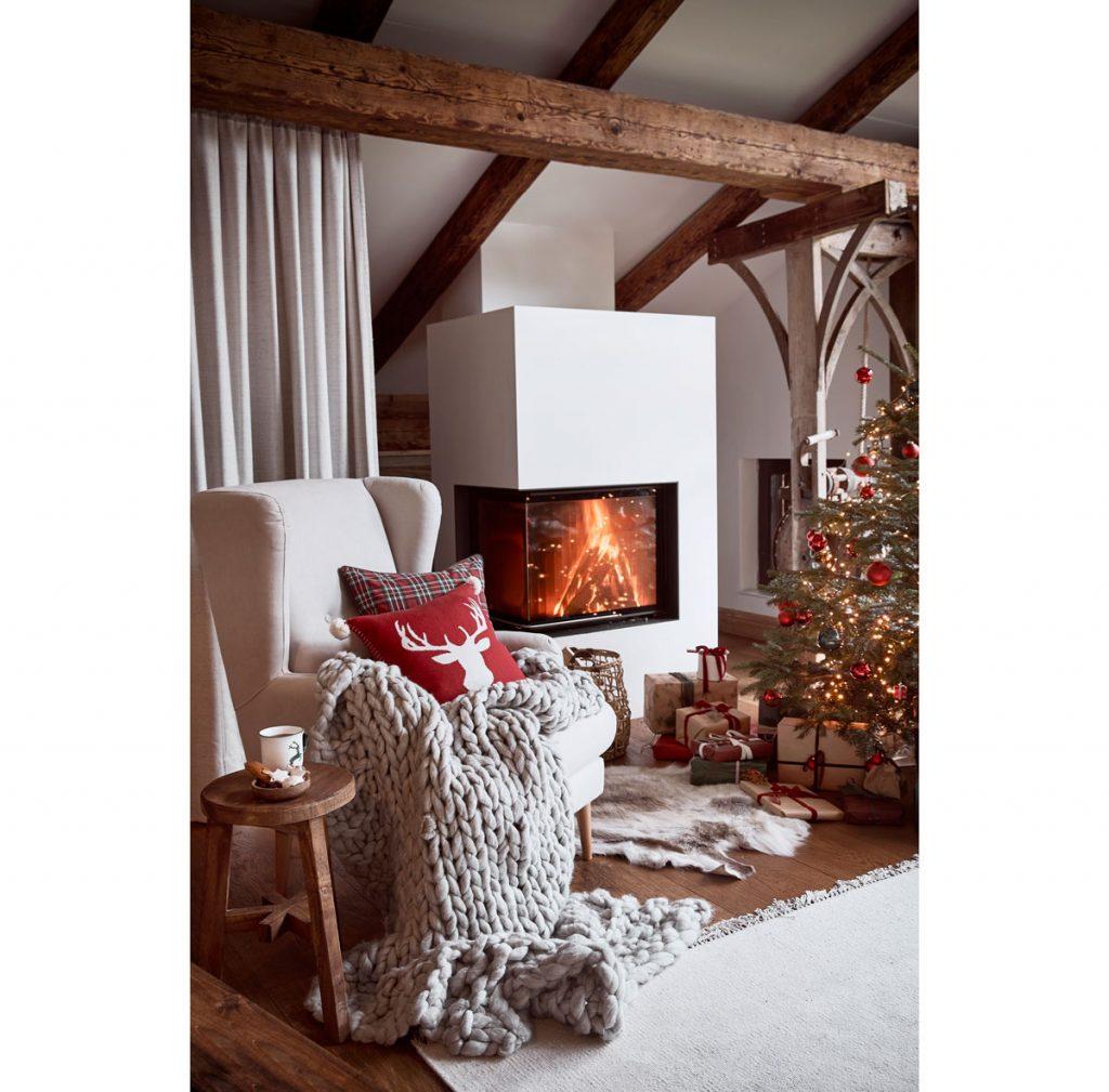 Vianočná obývačka s ušiakom s merino pletenou dekou a vankúšom so sobom, stromčekom s darčekmi a horiacim kozubom.