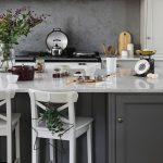 Menej tradičná vianočná výzdoba: kuchyňa s girlandou a kovovou hviezdou s vetvičkou ihličia a eukalyptu zavesenou na stoličke