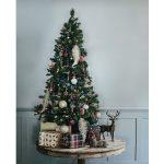 Inšpirácie na vianočný stromček: Malý stromček postavený na drevenom stolíku doplnený o dekorácie sobov