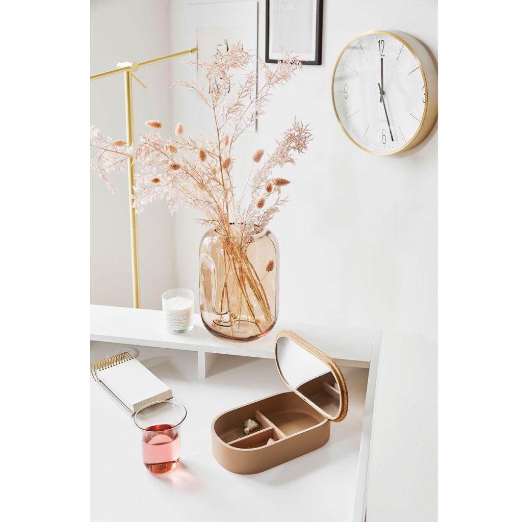 Biely stôl s presklenou vázou a šperkovnicou v hnedej farbe.