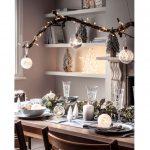 Menej tradičná vianočná výzdoba: vetva so svetielkami zavesená nad sviatočným stolom