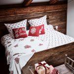 spálňa s drevenou posteľou a obliečkami s vianočným motívom sobov