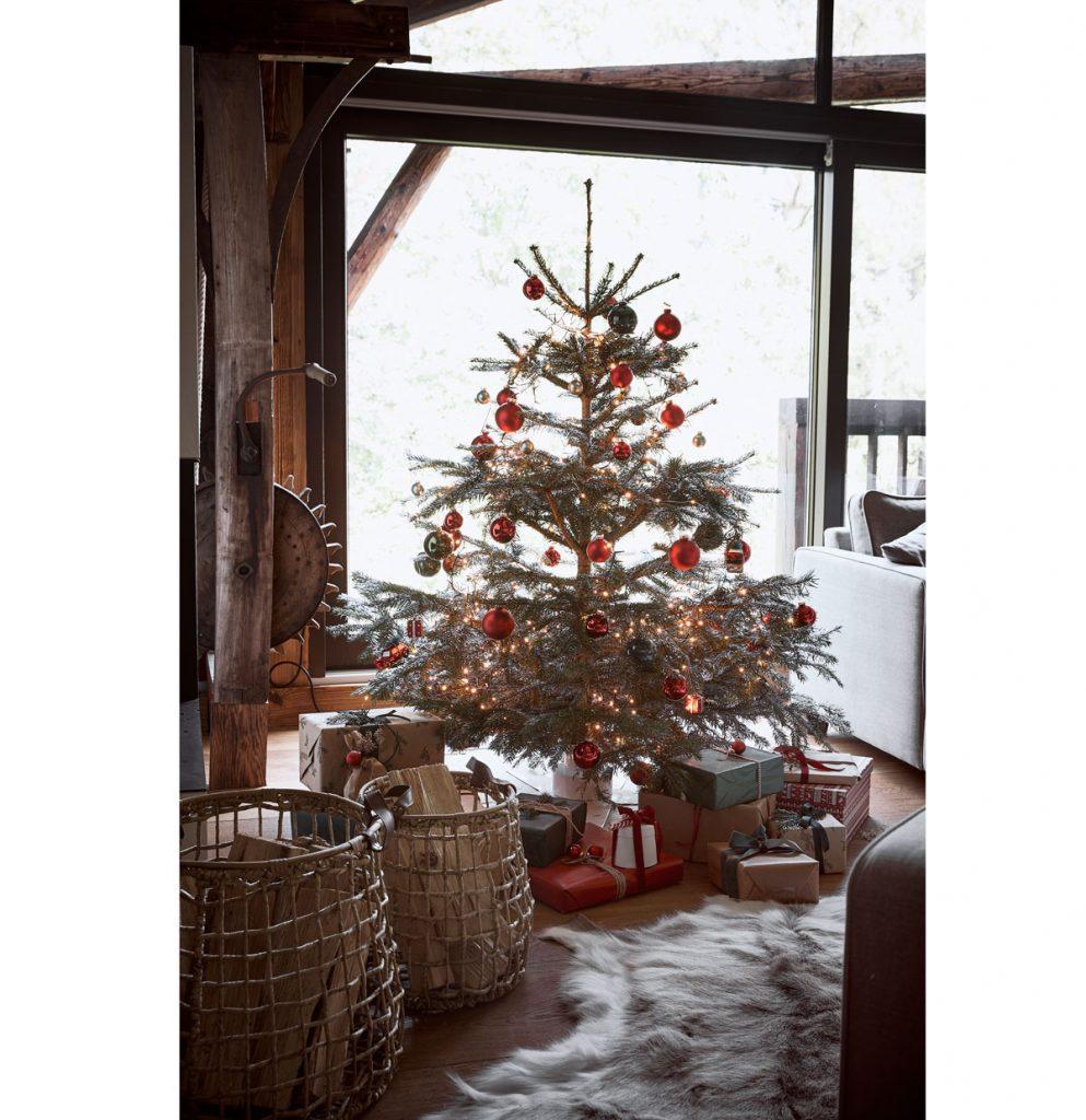 vidiecka obývačka s vianočným živým stromčekom, košmi na drevo a kožušinou