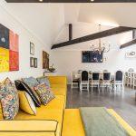 otvorený priestor jedálne a obývačky so žltou sedačkou do L a vankúšmi so vzorom kvetov