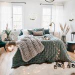 Menej tradičná vianočná výzdoba: spálňa so svetelnými reťazami, kvetinami vo vázach a vencom nad posteľou